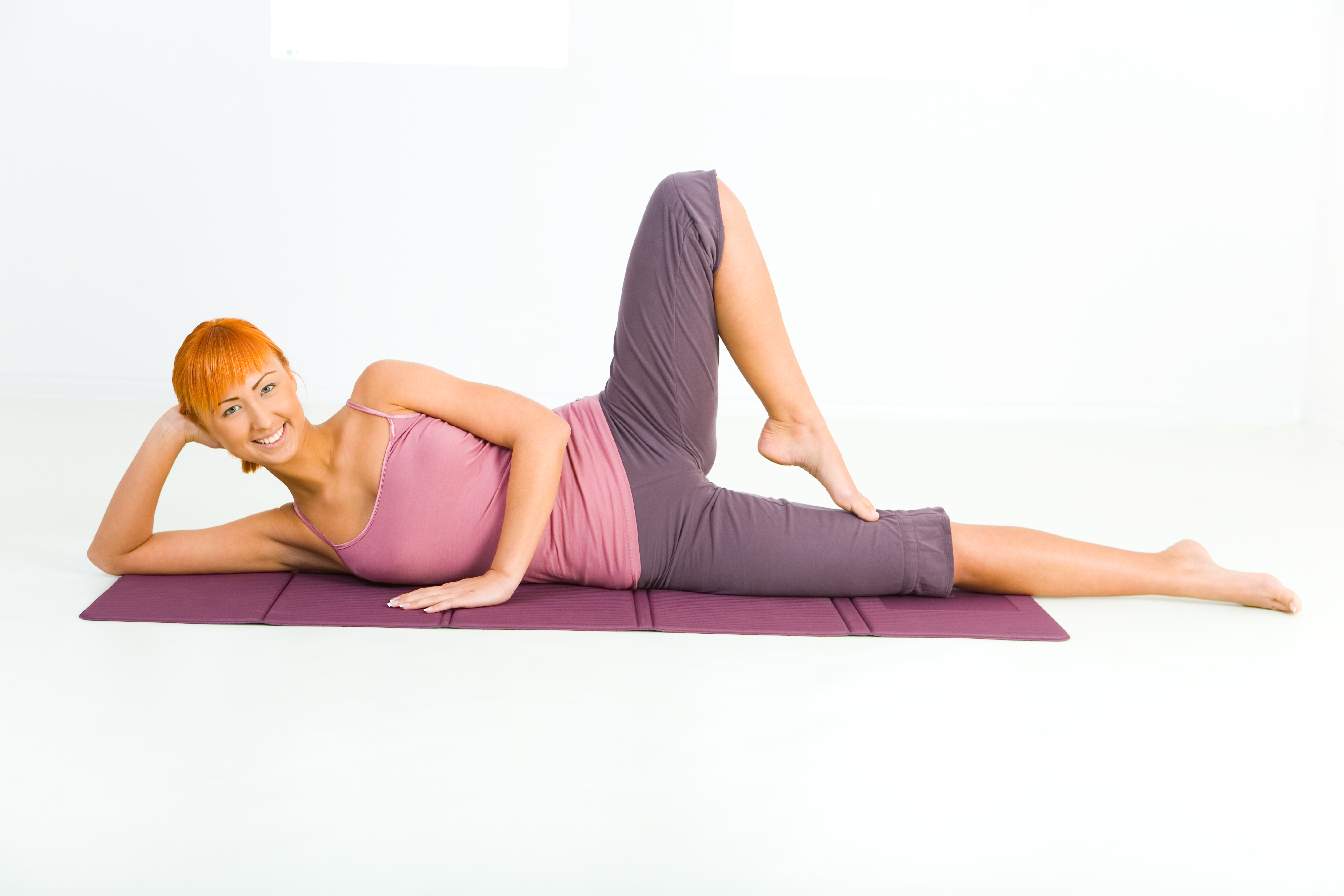 Woman laying down on her side on the floor doing a Pilates exercise move.