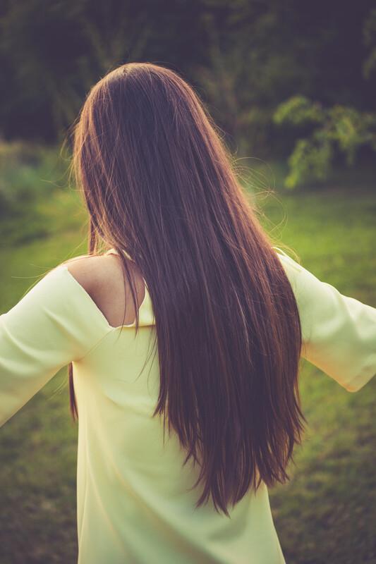 Women dancing on the grass with long beautiful hair.
