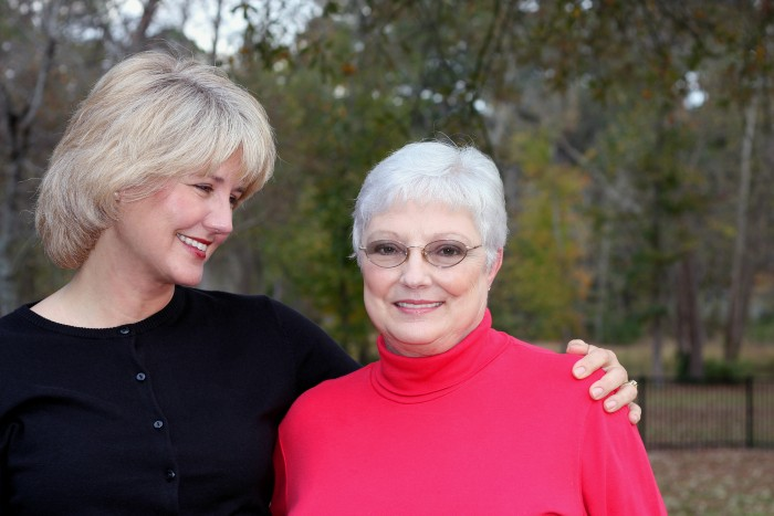 Senior mother and adult daughter hugging and smiling.